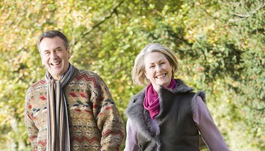 Senior couple walking through autumn woods