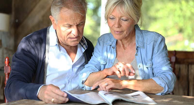 Senior couple in yard reading magazine